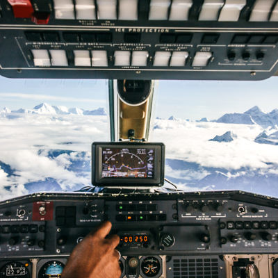 Airplane control cabin on a flight over Himalaya mountain range with Mount Everest on the background