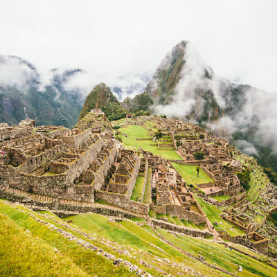 Machu Picchu Inca ancient ruins with clouds in Andes, Peru